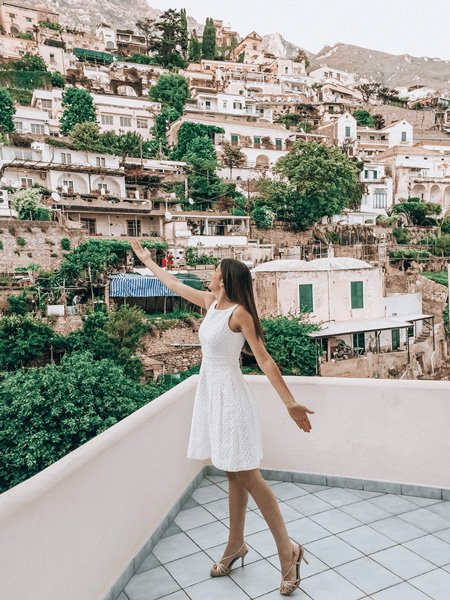 Brunette woman in a white dress with arms up toward Positano, Italy ledge pretending to be France Mayes in Under The Tuscan Sun