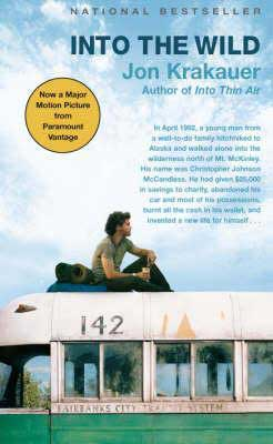 Into the Wild by Jon Krakauer book cover with young brunette man sitting on top of an old school bus