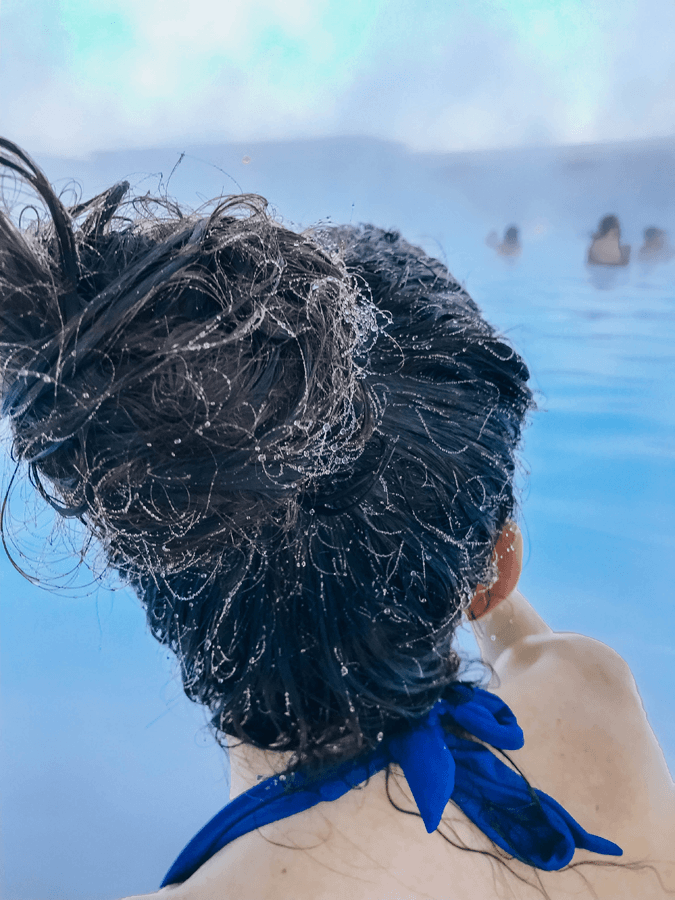 brunette woman in the Blue Lagoon Iceland with frozen hair