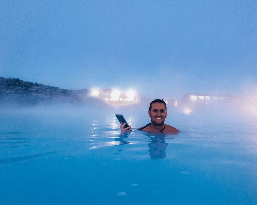 Brunette male in bathing suit in blue waters of Blue Lagoon Geothermal Spa Iceland holding a phone protector